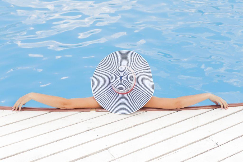 eine Frau mit einem blau-weiß geringelten Sonnenhut liegt mit ausgebreiteten Armen in einem Pool