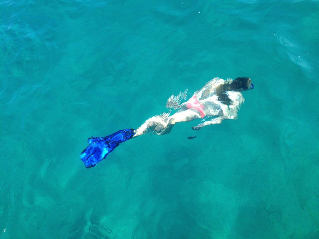 türkises Wasser, Frau im Bikini mit Schnorchel und Flossen taucht unter Wasser