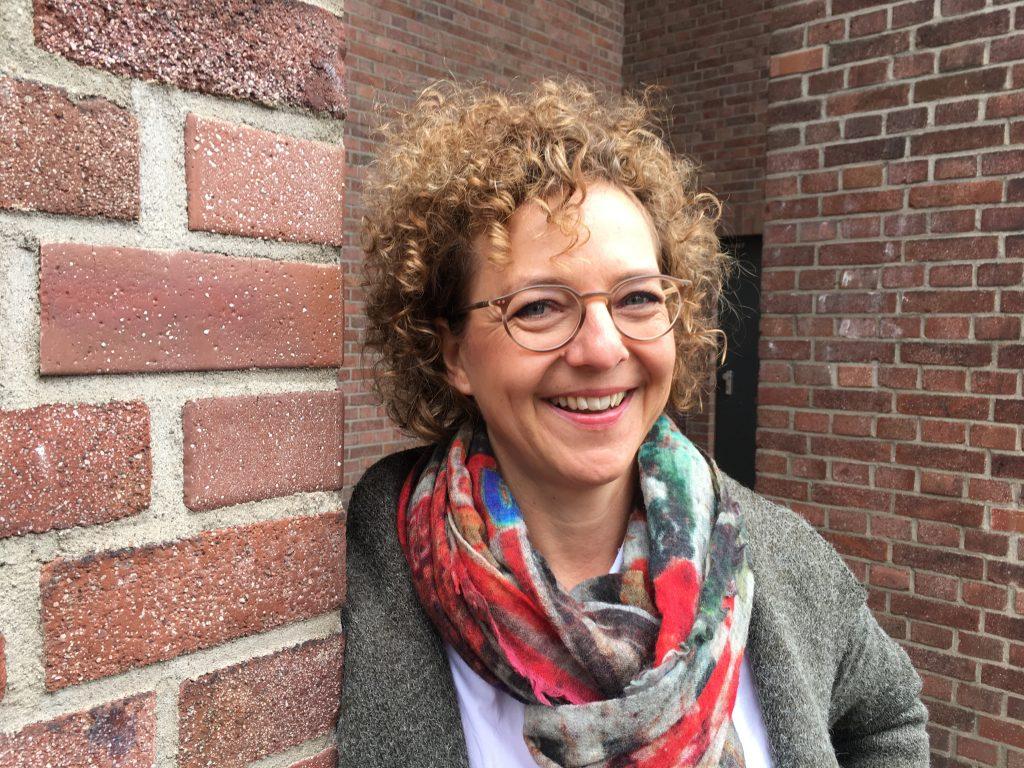 Autorin mit Brille und Locken steht vor einer Hauswand und guckt lächelnd in die Kamera