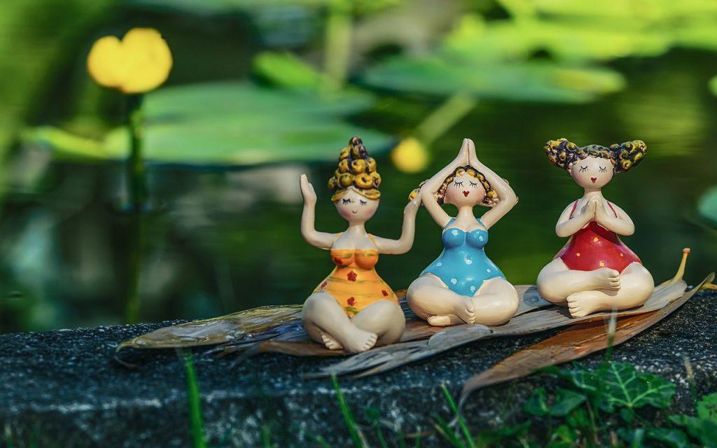 Drei weibliche Figuren sitzen in  verschiedenen Yoga-Positionen, Yoga als Mittel gegen Stress