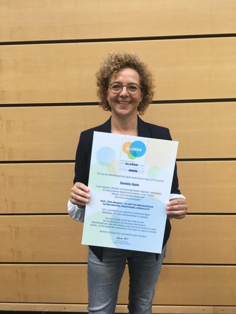 Frau mit Locken und Brille (Daniela Halm) mit dem Digital Health Heroes Award in der Hand
