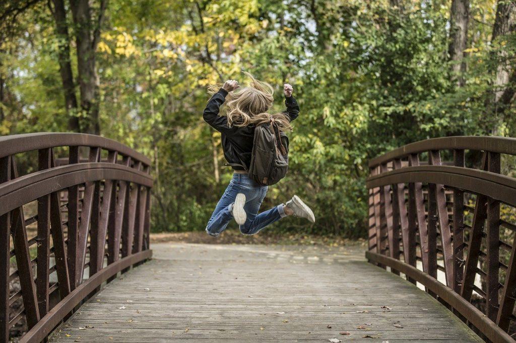 Kinder mit Allergien - blondes Mädchen mit Ranzen auf dem Rücken springt in die Luft