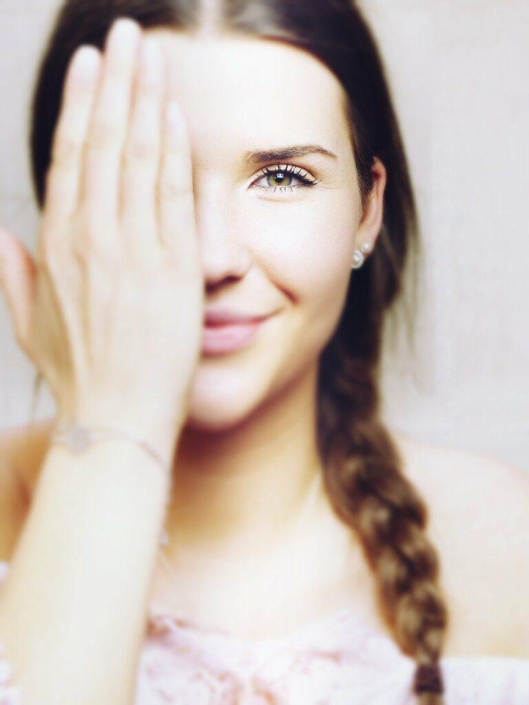 Eine junge Frau hält sich mit der Hand die rechte Gesichtshälfte zu