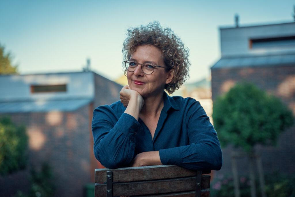 Frau mit Locken und Brille sitzt auf Stuhl, Autorin des Textes, es geht um das Thema loslassen