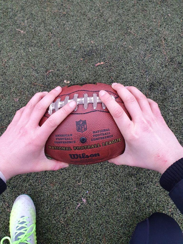 Zwei Hände mit Ekzem halten einen American Football auf Trainingsrasen