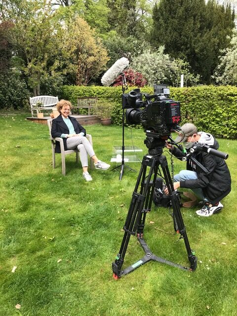 TV-Dreh im Garten, Frau mit Locken sitzt vor der Kamera und einem MIkrofon